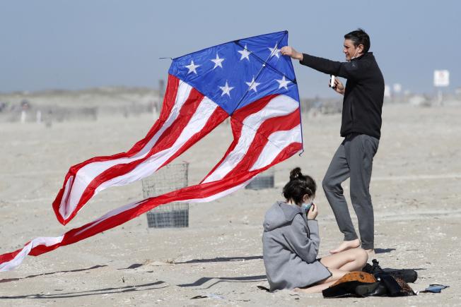 民眾在家避疫久了,國殤日長周末將有數百萬人出遊。圖為紐約瓊斯海灘上,一對伴侶 正在放風箏。(美聯社)