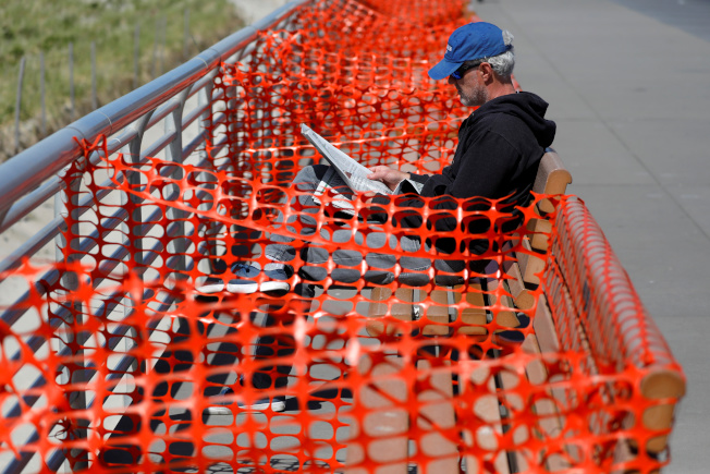 民眾在家避疫久了,國殤日長周末將有數百萬人出遊。圖為紐約長島一處海灘,一名男子坐在已關閉的長椅上閱讀。(美聯社)