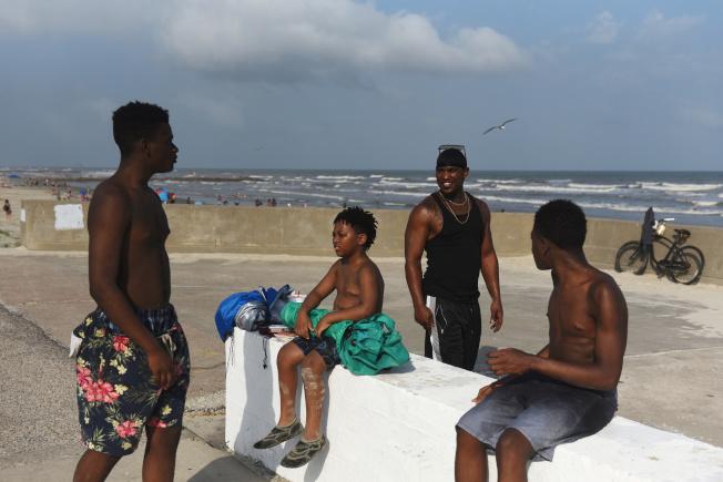 長周末正好出遊,公衛專家擔心疫情回升。圖為德州一個家庭正在海灘上透透氣。(路透)
