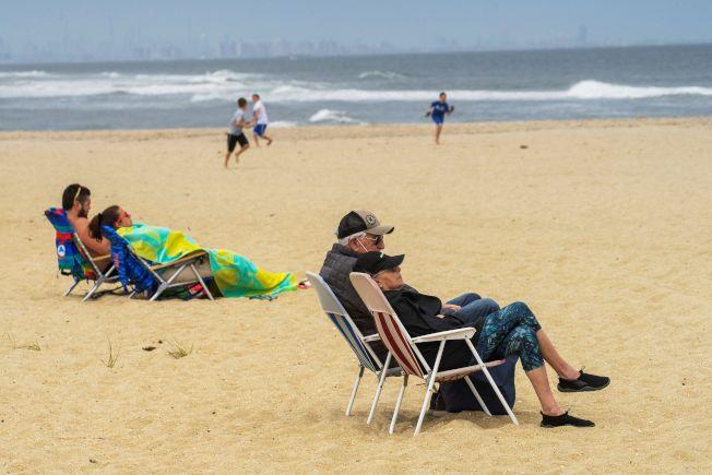 民眾準備在國殤日周末外出,公衛專家擔憂群聚恐導致疫情回升。圖為新澤西州桑迪胡克海灘上,遊客保持距離享受日光浴。(路透)