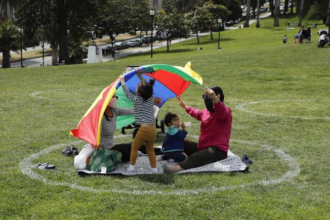 民眾準備在國殤日周末外出,公衛專家擔憂群聚恐導致疫情回升。圖為加州一處公園,全家人在草地上的白圓圈內嬉戲。(路透)