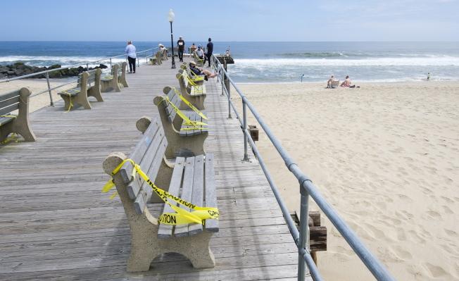 迎接國殤日長周末遊客,新澤西州一處海灘,在長椅上綁好布條,讓遊客保持距離。(歐新社)