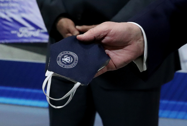 川普總統21日參訪密西根州的福特車廠時,曾戴上印有總統徽章的口罩,但之後摘掉沒再戴起。(路透)