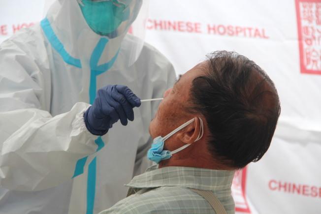 醫護人員全副裝備,為散房居民做新冠檢測。(記者李晗 / 攝影)