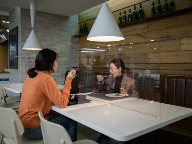 加州原來要重開的餐館,隔開進食的人,例如圖中以玻璃將人分隔,紐森已於本周放寬規定,因此灣區大部分縣都基本符合重開資格。(Getty Images)