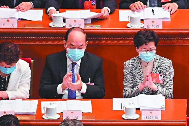 林鄭出席人大 香港特首林鄭月娥(右)22日出席北京舉行的全國人大會議,她表示會全力配合港版國安法的立法工作。(法新社)