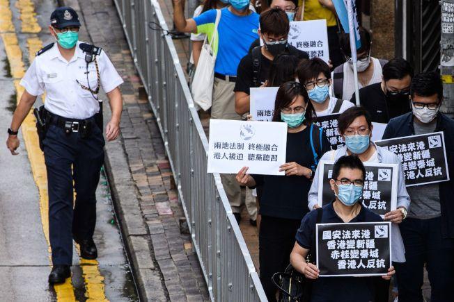 香港民主派示威者22日前往中聯辦舉牌抗議,呼籲港人起身反抗中國人大將審議的港版國安法,警告將讓香港變成新疆。香港民間人權陣線擬發動兩百萬人的抗爭。(Getty Images)