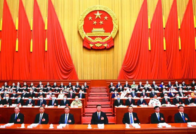 中國13屆全國人大三次會議22日在北京開幕,第一排的常委們均未佩戴口罩,後方主席台官員與台下的與會代表們全數戴上口罩(見圖)。李克強總理作政府工作報告。(新華社)
