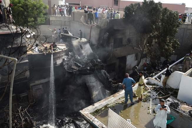 巴基斯坦客機墜毀,消防人員對失事的飛機殘骸灑水降溫。(Getty  Images)