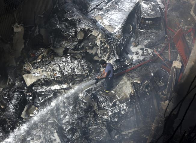巴基斯坦客機墜毀,一名消防員試圖飛機失事引發的火災。(美聯社)