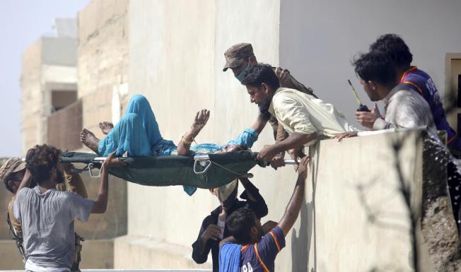 巴基斯坦客機墜毀喀拉蚩住宅區,救難人員搶救出傷者。(美聯社)