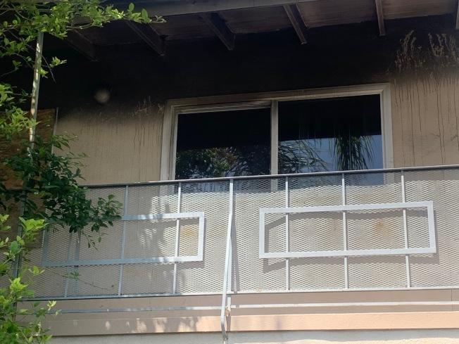 亞市一幢公寓起火,遠遠可見屋頂煙熏痕跡。(記者張宏/攝影)