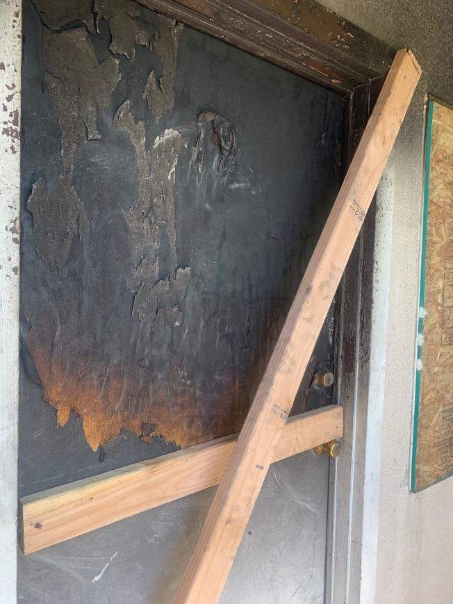 室門被火燒毀,消防員用板條封閉起來。(記者張宏/攝影)