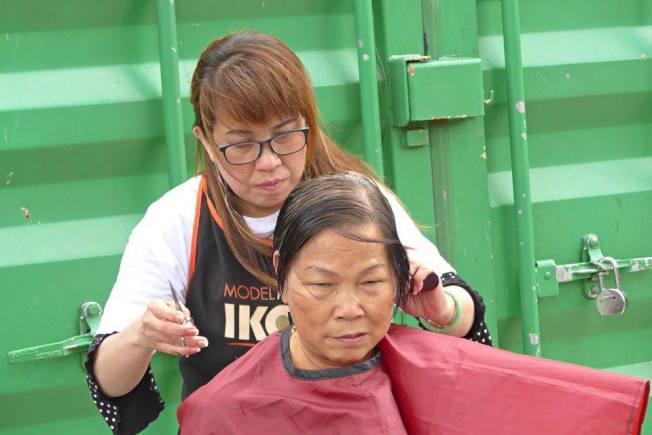 一名華裔義工為耆老剪頭髮。(取自黎怡臉書)