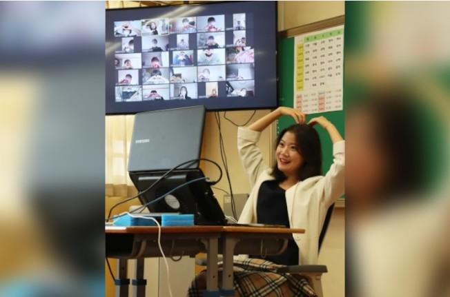 南韓京畿道城南市一名中學老師14日在線上授課時比出愛心。(歐新社)