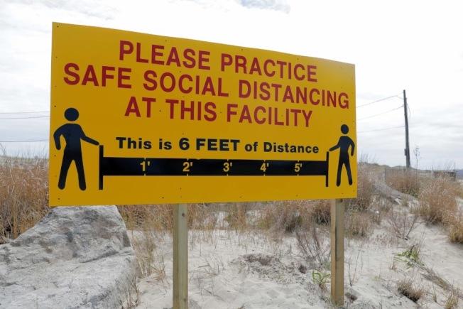 海灘上豎起牌子提醒民眾保持社交距離。(路透)