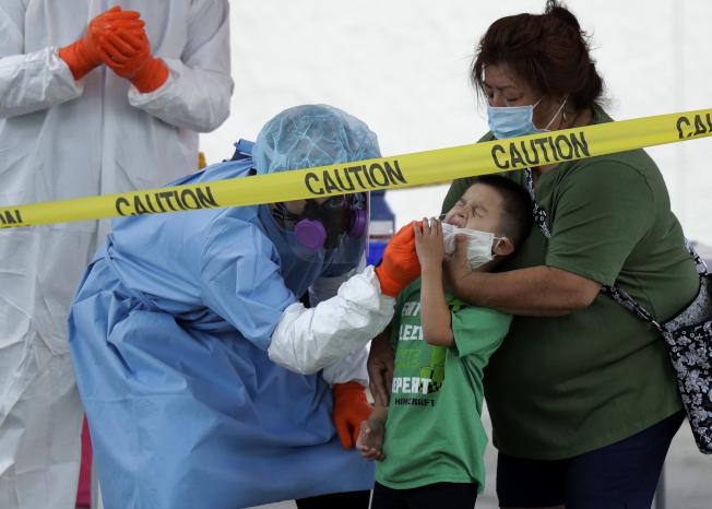 聯邦疾病防治中心與多州官員坦承混合病毒檢測與抗體檢測的資料。圖為德州聖安東尼奧一名男童(中)被祖母(右)架住頭接受新冠病毒檢測。(美聯社)