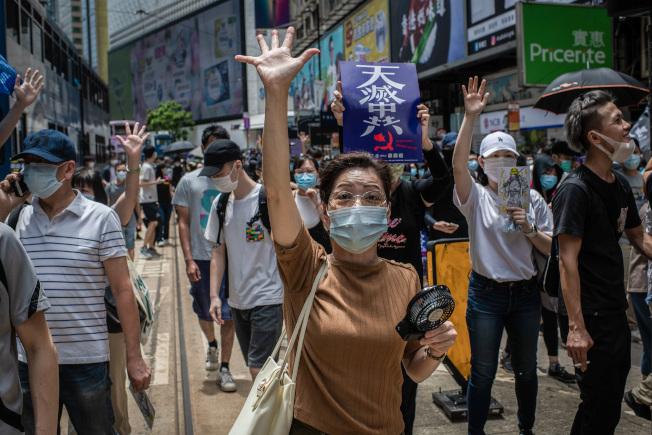 參加24日反港版國安法大遊行的一名戴著口罩的婦女舉出五指,表達「五大訴求」的反送中使命。(Getty Images)
