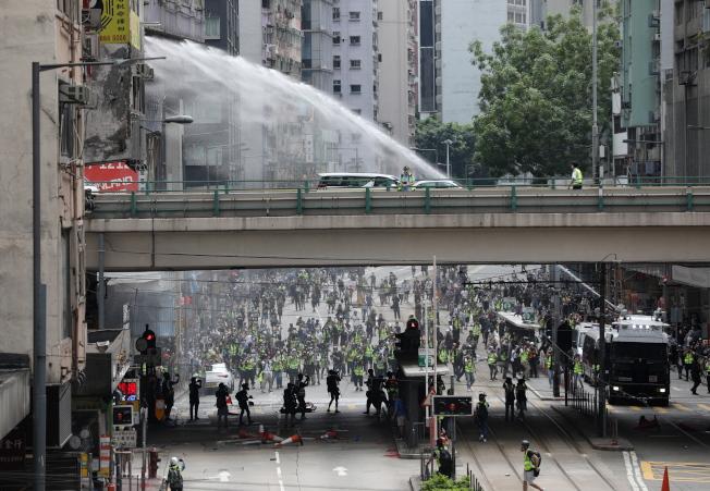 大批香港民眾23日下午齊聚銅鑼灣舉行抗議港版國安法的「反惡歌法大遊行」活動,警方出動水炮車發射水柱驅散民眾。(歐新社)