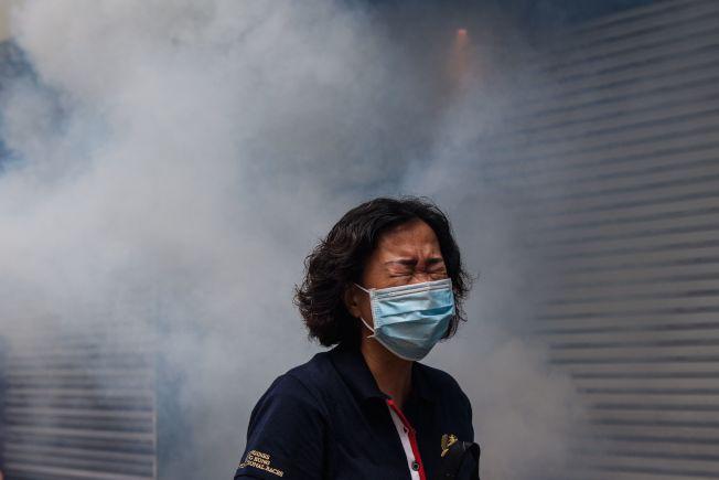 一名戴著口罩的香港婦女24日被港警摧淚彈煙霧包圍。(Getty Images)