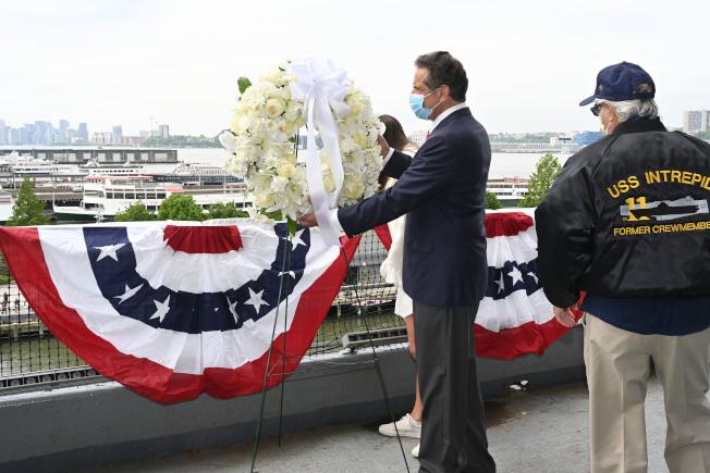葛謨25日在紐約市登上無畏號航空母艦博物館,向水中投擲花圈,紀念陣亡將士。(州長辦公室提供)