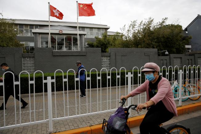 正在北京舉行的中國人大會議,將於28日審議表決港版國安法。圖為戴口罩的民眾經過香港行政特區政府在北京的辦事處。(路透)