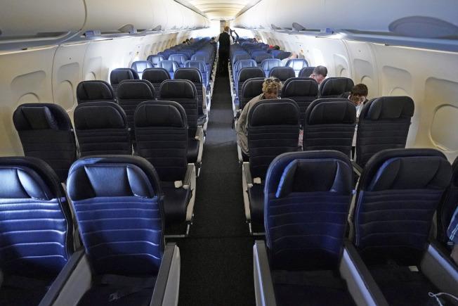 各州陸續解封,航空酒店房貸等行業,顯示復甦跡象。圖為國殤日長周末24日的自休士頓起飛的聯合航空的班機上,乘客仍是稀少,幾乎是空機。(美聯社)