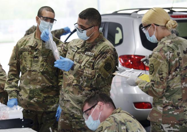 州陸續解封,但公衛專家擔心今夏新冠病毒將會捲土重來。對全民新冠病毒檢測追蹤,異常重要。圖為伊利諾州國民兵出動,協助州民進行檢測。(美聯社)
