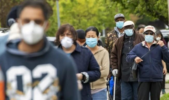 法國最新研究發現,新冠患者有短期免疫力,圖為5日紐約市皇后區居民排隊領取免費口罩畫面。美聯社