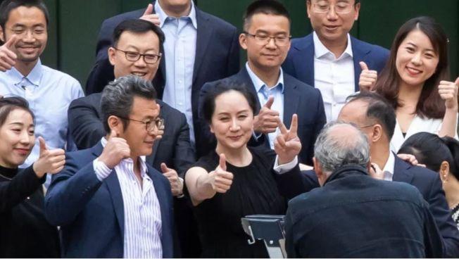 孟晚舟在法院門口拍照並開心比出大拇指。(取材自CBC官網)