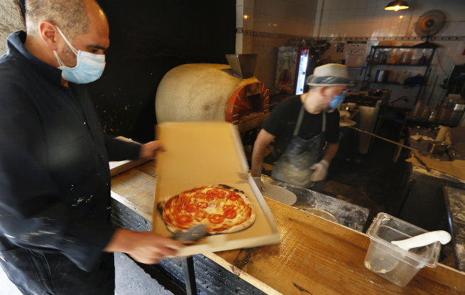 疫情期間,全國最受歡迎的外送餐點是「披薩」。圖為店員準備外送披薩。(美聯社)