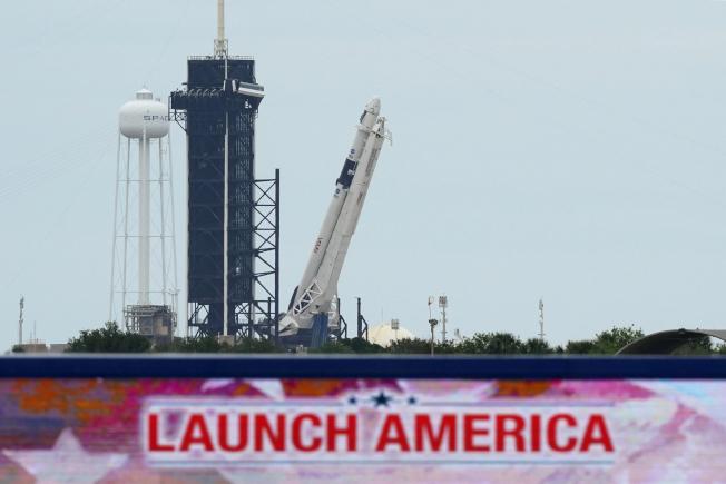 太空探索科技公司SpaceX將於27日下午發射「獵鷹9號」火箭,將兩名太空人送上國際太空站。這是近10年以來首次在美國本土發射載人箭的太空飛行。圖為26日佛州卡納維拉爾角的甘迺迪太空中心,寫有「美國升空」字樣的發射台上,搭戴太空艙「飛龍號」的「獵鷹九號」火箭,整裝待發。(美聯社)