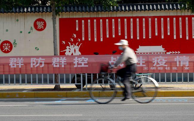 一場新冠疫情深刻傷害中國經濟,圖為民眾戴著口罩從疫情防控宣傳標語前經過。(中新社)