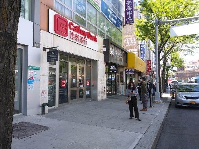 在法拉盛的緬街上,人們排隊進入銀行,仍然保持社交距離。(韓傑/攝影)