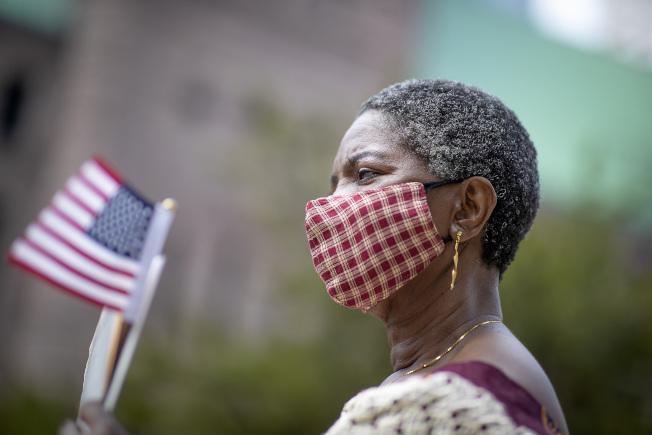 明尼蘇達州一名女子戴著口罩在戶外參加入籍儀式。(美聯社)