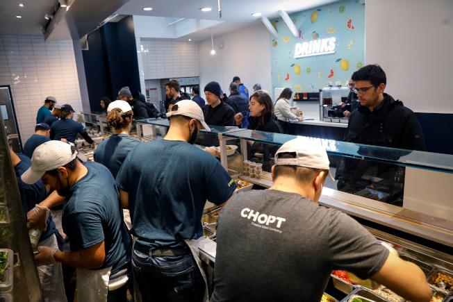 餐廳、連鎖速食店和飯店是人們最可能感染新冠病毒的三大場所。圖為一家速食店的員工正在準備餐點。(路透)