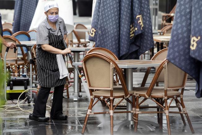 餐廳、連鎖速食店和飯店是人們最可能感染新冠病毒的三大場所。圖為華府一家餐館的員工正在清潔。(美聯社)