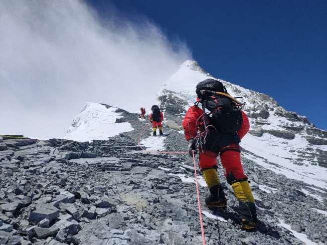 26日16時35分,6名修路隊員將攀登路線打通至珠峰峰頂,即把路繩鋪設至珠峰峰頂,為登頂測量打下良好基礎。(新華社)