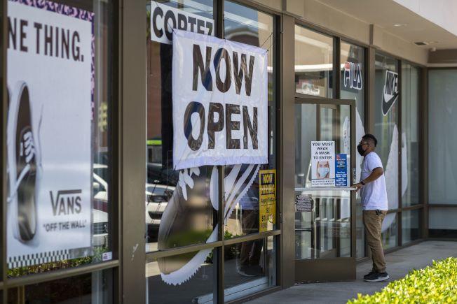 許多民眾察覺自己可能染疫,CDC新版建議指南指出,如果符合三項條件,就可以恢復與人接觸。圖為加州部分商業活動重啟,一家鞋店在門口貼上「現在開門營業」的標示。(Getty Images)