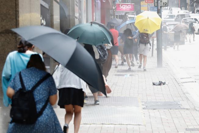 香港鎮暴警察發射胡椒球彈驅散示威者,人們紛紛以傘遮擋。(路透)