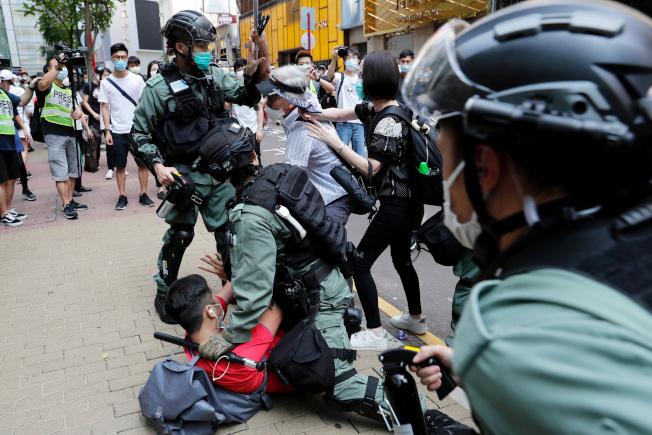 香港示威者抗議「國歌法」二讀,與鎮暴警察當街扭打。(路透)