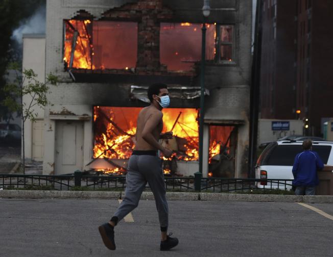 明尼亞波利斯市抗議警察暴力的示威27日晚進入第二晚,演變成搶劫攻擊,圖為該區的汽車零件商店遭人縱火。(美聯社)