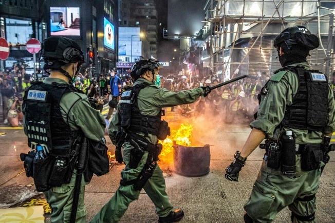 香港立法會27日進行「國歌法二讀」辯論,鎮暴警察當天在旺角區驅散堵住道路的示威者。(Getty Images)