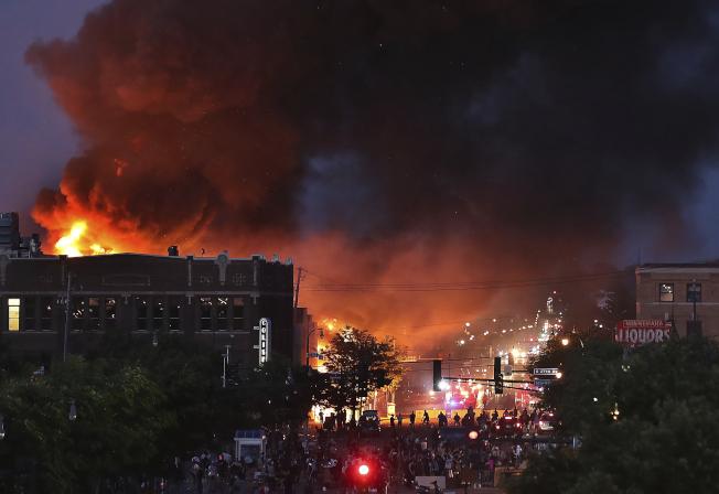 明尼亞波利斯市暴亂動盪,火光照亮夜空。(美聯社)