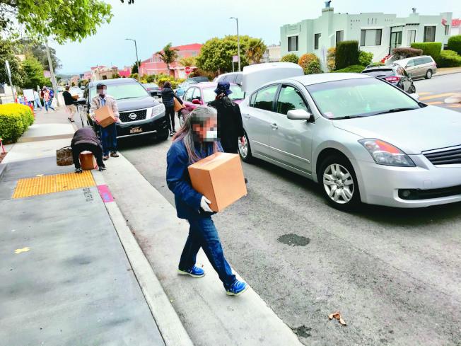 舊金山西南邊某食物派發站外面的馬路上停滿私家車,不少人將領到的食物裝到車上帶回家。(讀者提供)