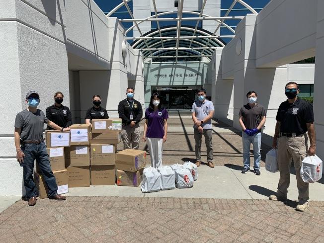 薩拉度加市議員趙嬿(左五)與社區人士到聖他克拉拉縣警局捐贈口罩與食物。(記者李榮/攝影)