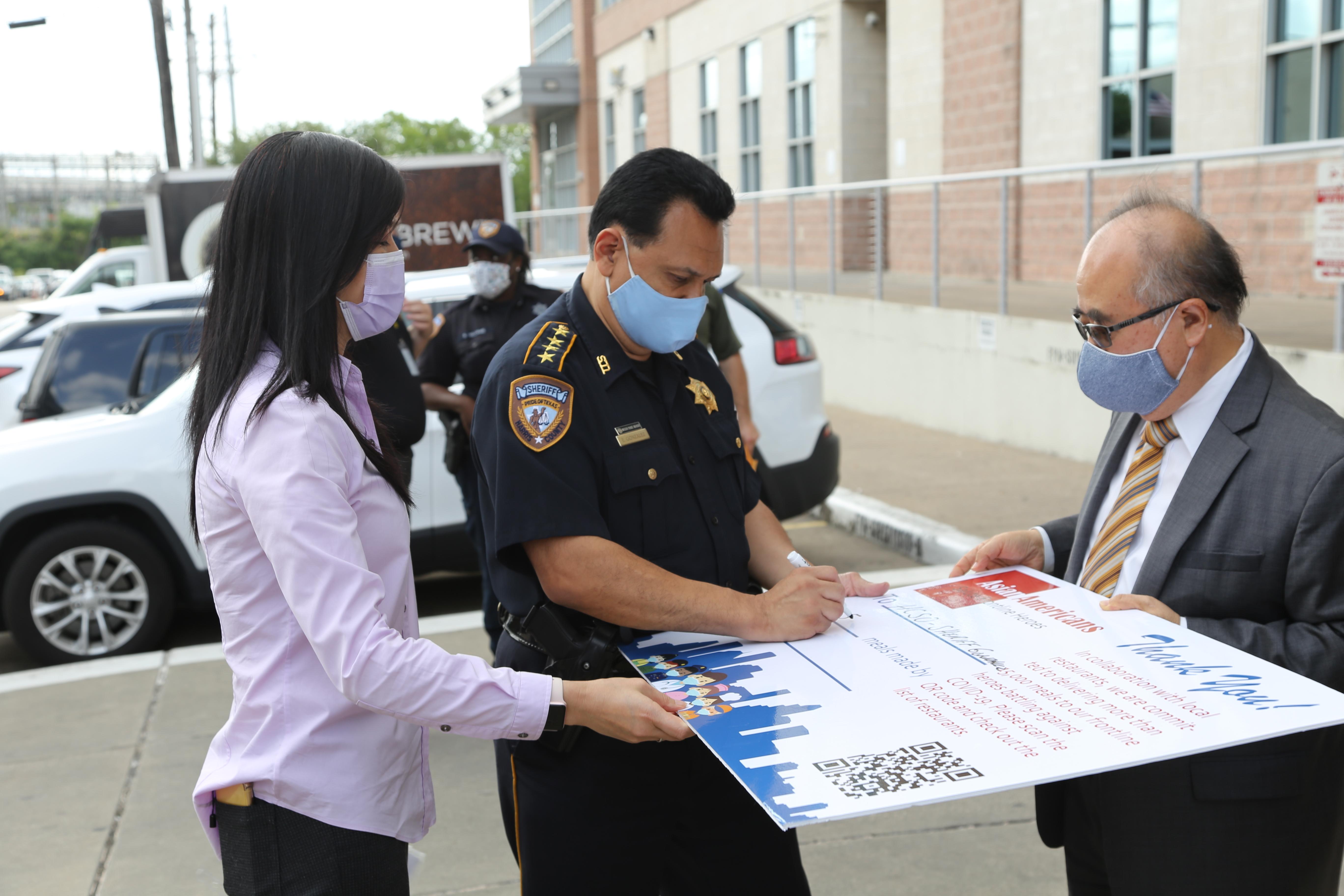 警長岡薩雷茲(中)親自在看板上簽字,感謝亞裔美國人的貢獻。(記者封昌明/攝影)