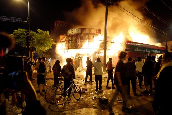 明州暴民28日深夜攻進明尼亞波利斯警局第三分局,現場可見火光沖天。(路透)