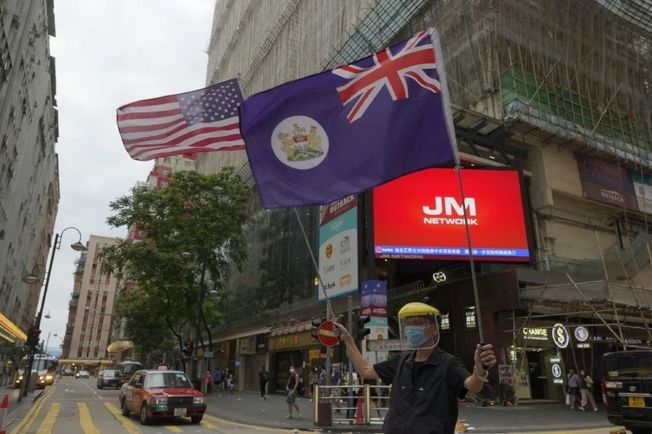 基於對港版國安法的疑慮,中國富豪停泊在香港的資金預料會愈來愈少。圖為手持美國國旗與港英時期香港旗的香港示威者。(美聯社)