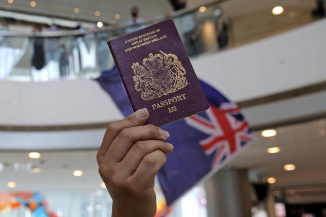 香港示威者29日在商場拿著英國國民海外護照,抗議大陸全國人大決定制定港版國安法。(美聯社)